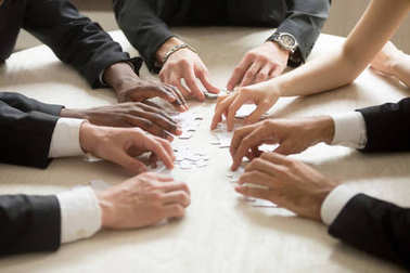 Diverse business team assembling jigsaw puzzle, hands joining pieces on desk in office, group of people playing board game, corporate common goal, help and support in teamwork concept, close up view