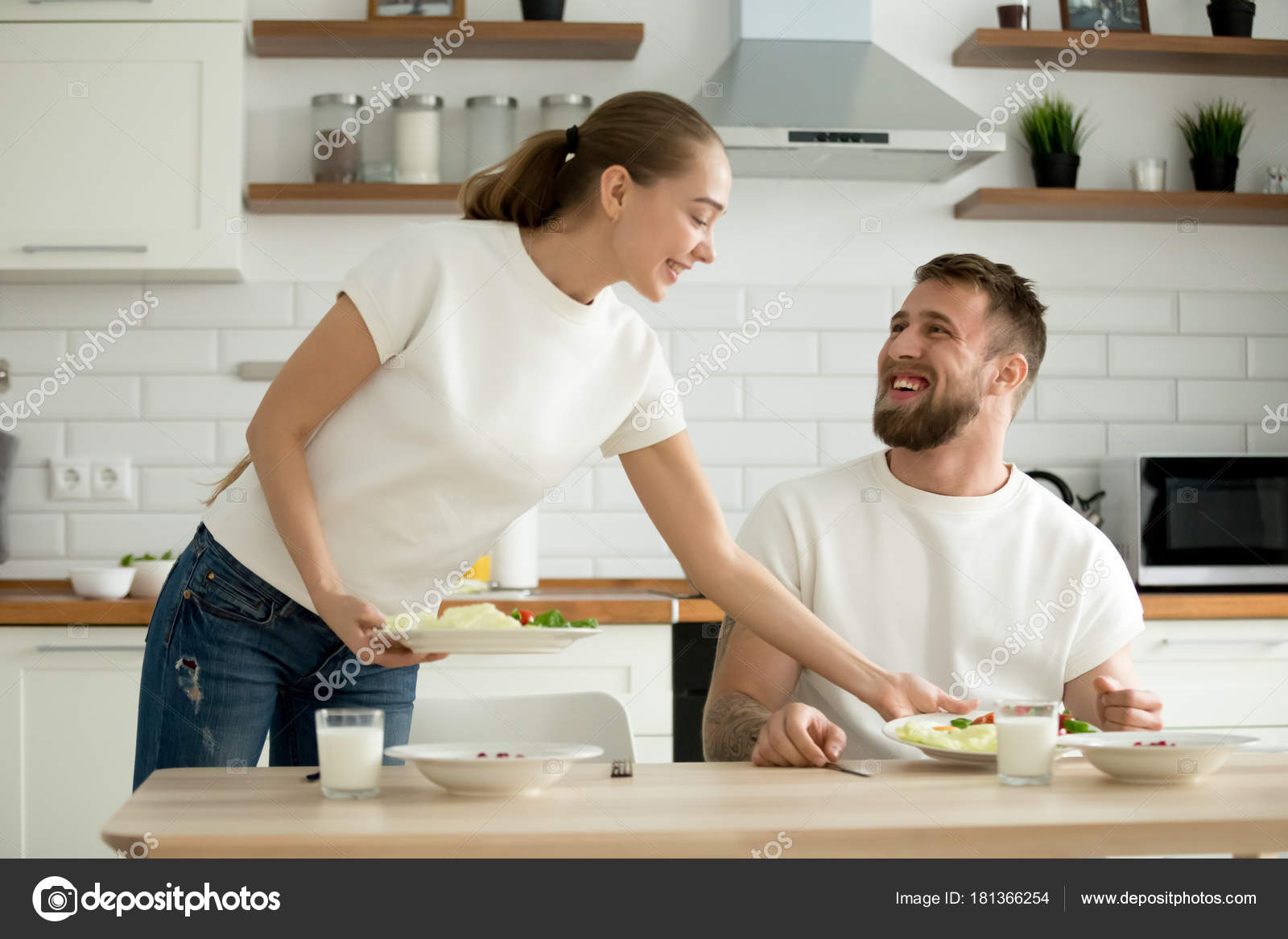 Attractive wife serving food cooked for husband in the kitchen ...