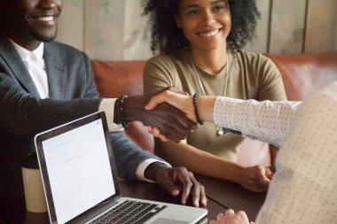 Happy african american couple making deal handshaking caucasian