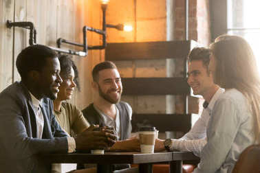 Multiracial young friends talking and drinking coffee sharing co
