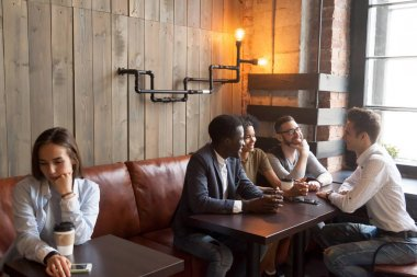 Diverse young friends ignoring sad girl sitting alone in cafe