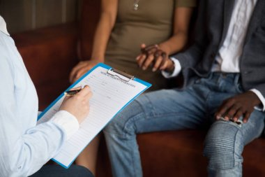 Psychologist filling medical patient information form consulting
