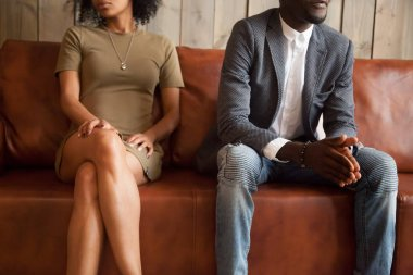 African-american couple sitting on couch after quarrel, bad rela