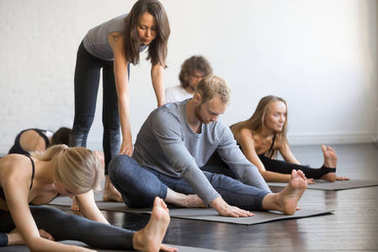Young female yoga instructor teaching Head to Knee Forward Bend