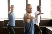 Gruppe von sportlichen Menschen, die in Krieger zwei Übung stehen