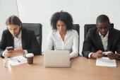 Gemischtrassig Geschäftsleute sitzen am Bürotisch mit Koop