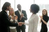 Photo Grateful boss handshaking promoting african businesswoman congra