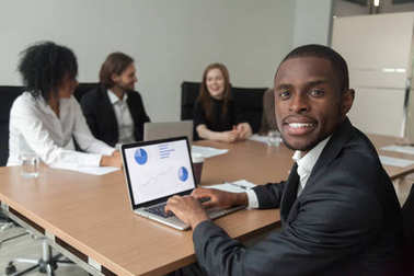 Smiling african-american businessman using laptop looking at cam