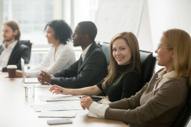 Young smiling businesswoman looking at camera at corporate group