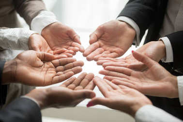 Diverse multi-ethnic business team members join helping hands group together palms up as concept of involvement, contribution in common goal, supporting unity and crowdfunding donation, close up view