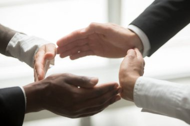 Hands of multiracial african and caucasian people group join in circle as concept of successful unity, help and support in teamwork, commercial insurance or business protection concept, close up view