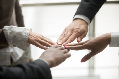 Hands of four diverse partners join together, multi-ethnic business team members touching fingers promising help and unity in common goal achievement, support in collaboration concept, close up view