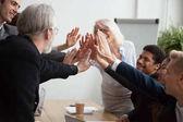 Imprenditori giovani e senior multirazziale unire le mani dando Ciao