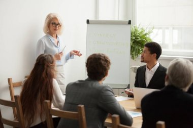 Aged attractive businesswoman giving presentation at corporate t