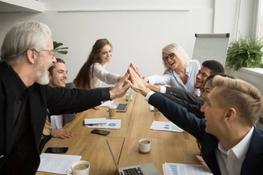 Diverse motivated young and senior business people giving high f