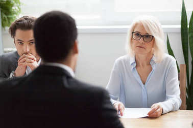 Serious attentive senior hr listening to candidate at job interv