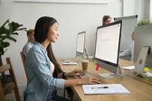 Mladá Asijská podnikatelka pomocí počítače práci v režimu online v cowor