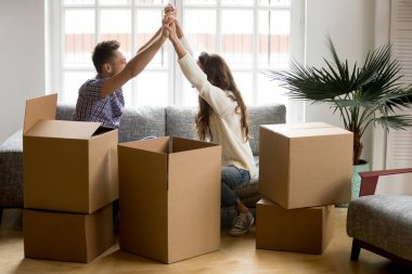 Excited couple holding hands happy to move into new home