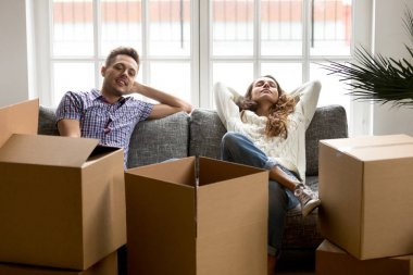 Happy couple relaxing on couch after moving in new home