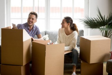Happy couple having fun laughing unpacking boxes on moving day