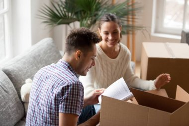 Young man holding book helping wife packing on moving day