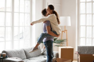 Excited couple celebrating moving day, man lifting embracing hap