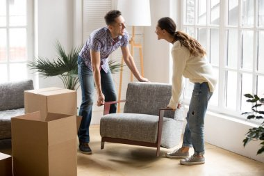 Couple carrying chair together, placing furniture moving in new