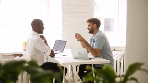 African american and caucasian young businessmen talking laughing at workplace