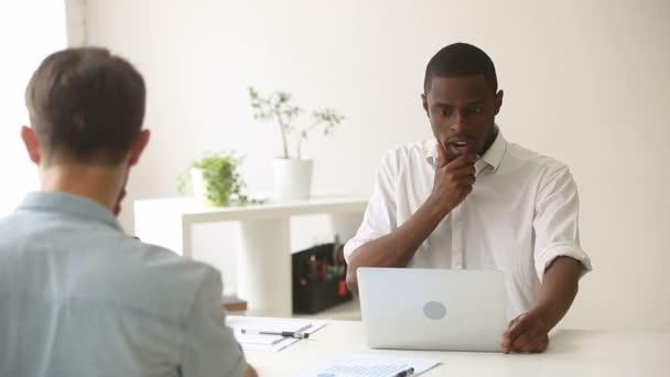 Překvapený afroamerické vítěz vyhrál online při pohledu na přenosný počítač v kanceláři