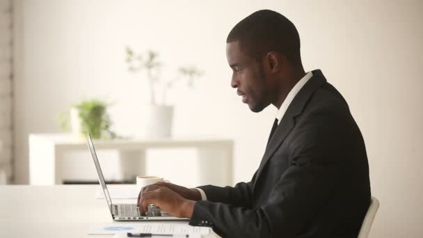 African american businessman working on computer sitting at office desk