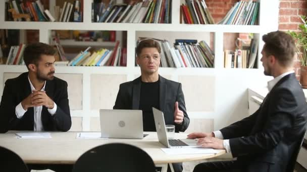 Successful businessman negotiating with business partners at meeting with laptops