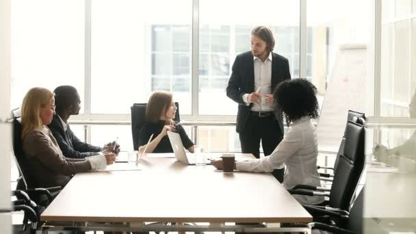 Diverse businesspeople discuss presentation with speaker at meeting in boardroom