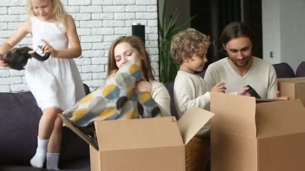 Famiglia felice con i bambini disimballaggio scatole entrano nella nuova casa