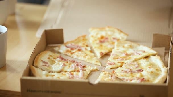 Ruce s kousky krájené pizzy z otevřené krabice, closeup