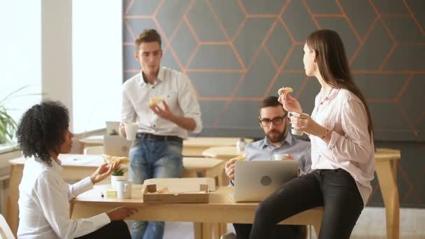 Mladí lidé těší, jíst pizzu, oběd v kanceláři