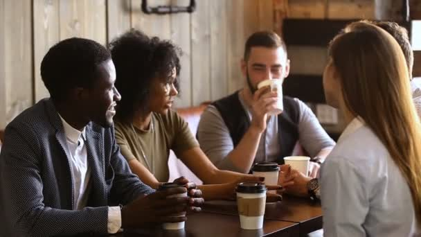 Mnohonárodnostní skupiny přátel pití kávy společně v útulné kavárně