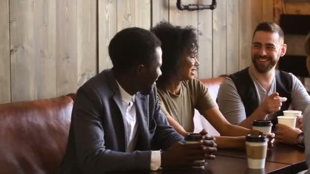 Multi-ethnic friends enjoying drinking coffee meeting together in cozy coffeeshop