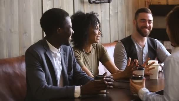 Diverse young guys spending time together in cafe drinking coffee