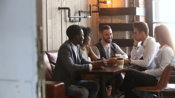 Rozmanité mladí přátelé mluví pití kávy v útulných podkroví kavárny