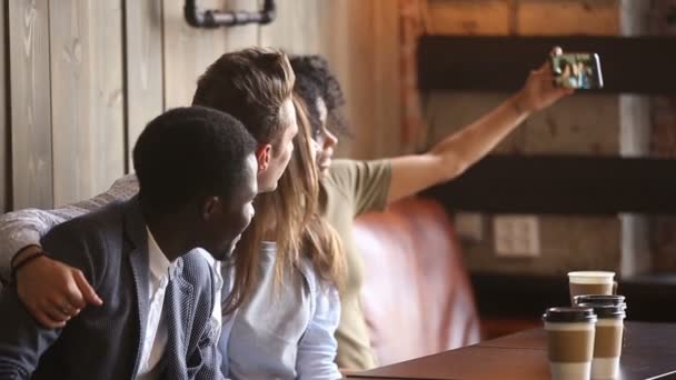 African-american woman taking group selfie at meeting with diverse friends