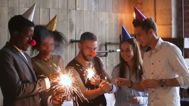 Happy multi-ethnic friends lighting sparkles celebrating together in party hats