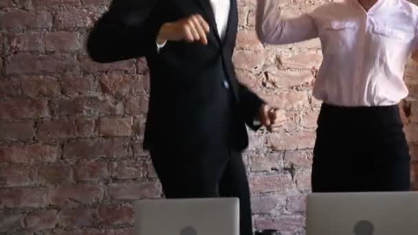 Excited employees celebrating success with funny victory dance in office