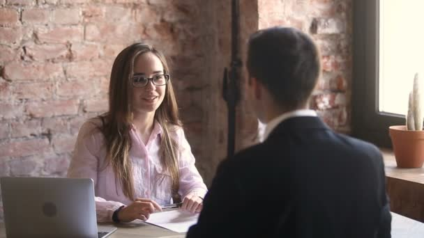 Young friendly hr manager holding interview with candidate in office