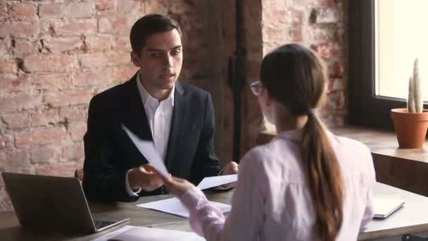Businessman and businesswoman arguing about documents, disagreeing pointing at papers