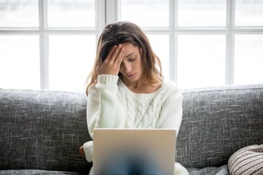 Frustrated woman worried about problem sitting on sofa with lapt