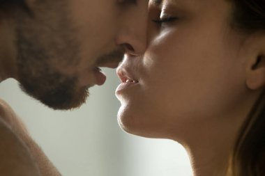 Sensual couple kissing, faces and lips close up side view