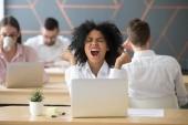 Happy vzrušený afroamerické zaměstnance slaví o online win