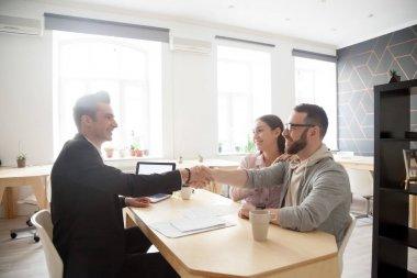 Happy millennial couple handshaking smiling financial advisor, l