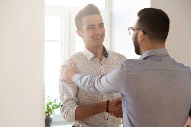 Grateful boss handshaking employee congratulating with job promo