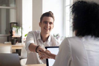 Smiling millennial man handshaking african female coworker celeb